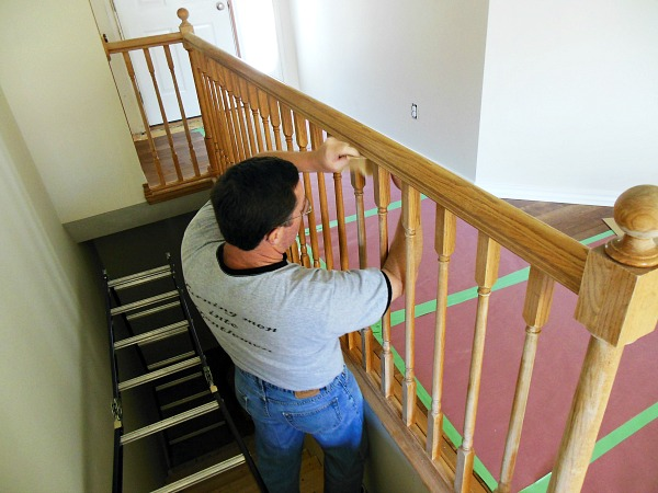 Sanding the stair railing before priming and painting.
